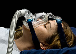 Female Demonstrating How a CPAP Face Mask is Installed and Used